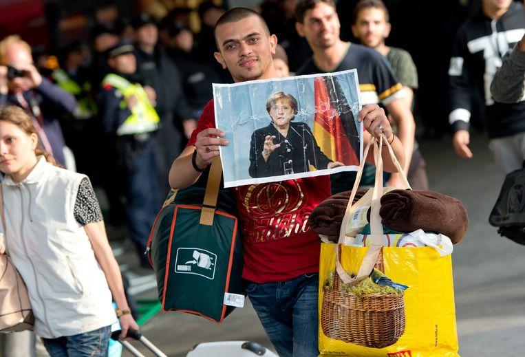 Een vluchteling op het station van München houdt een foto van de Duitse bondskanselier Angela Merkel omhoog. Beeld EPA