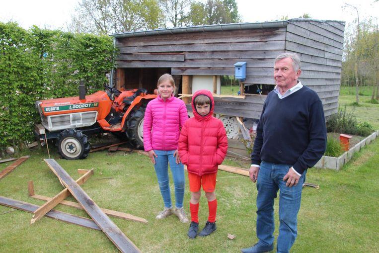 Fleur (11), haar broer Maxim (8) en opa Jozef bij het tuinhuis waar papa Hans in reed met zijn zitmaaier.