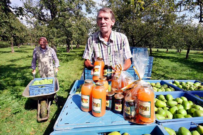 Coördinator Arie Versluis met vrijwilliger Johan Stevens bij de oogst en sap-producten die van het hoogstamfruit gemaakt worden.
