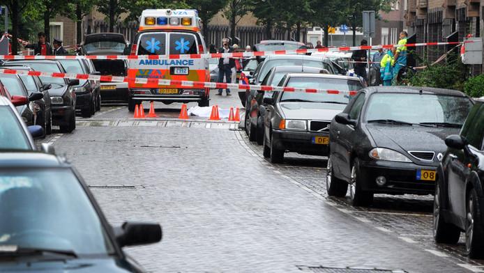 Een ambulance staat in een straat in Amsterdam-West in 2010. Onder het witte doek ligt het lichaam van een man. Volgens een aantal media zou het om een liquidatie in de onderwereld gaan.