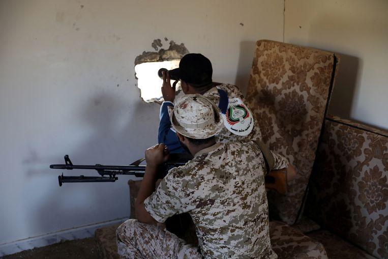 Militairen van het regeringsleger van Libië speuren in de buitenwijken van Tripoli naar troepen van de krijgsheer Haftar die de Libische hoofdstad proberen in te nemen. Beeld Reuters