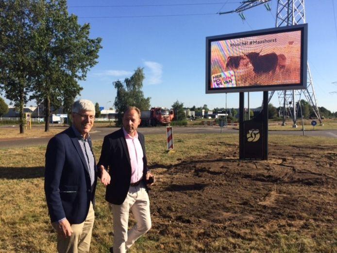 Ondernemers Ties van Donzel en wethouder Ben Tuithof bewonderen het niewue led-scherm op de kop van de Industrielaan.