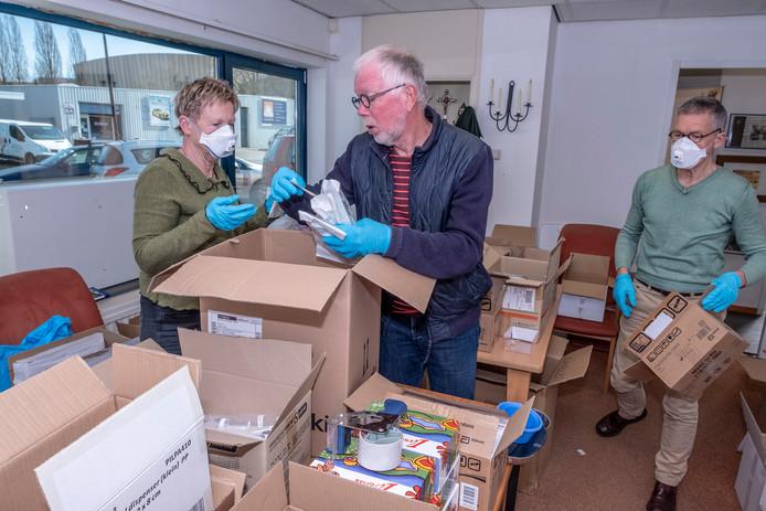 Vrijwilligers Anneke Meijsen, Rob Schuurman (m) en Perry van Kempen gaan door de voorraad dozen van de stichting heen.