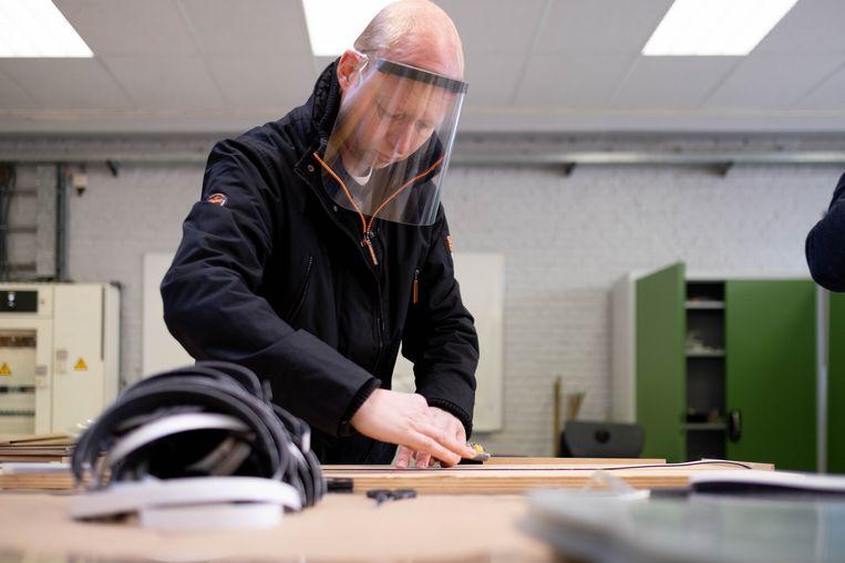 Een leerkracht maakt een faceshield (archiefbeeld, niet in Kortrijk).