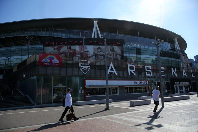 Een man met een mondkapje voor het Emirates Stadium van Arsenal.