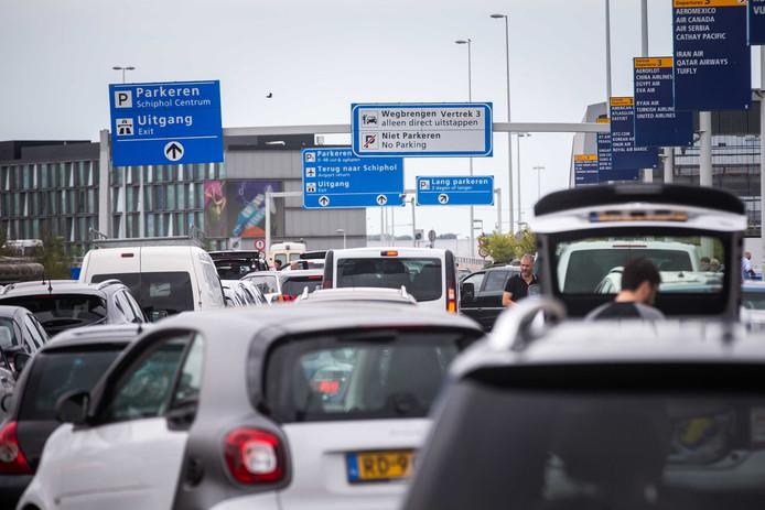 Reizigers bij de Kiss and Ride van Schiphol
