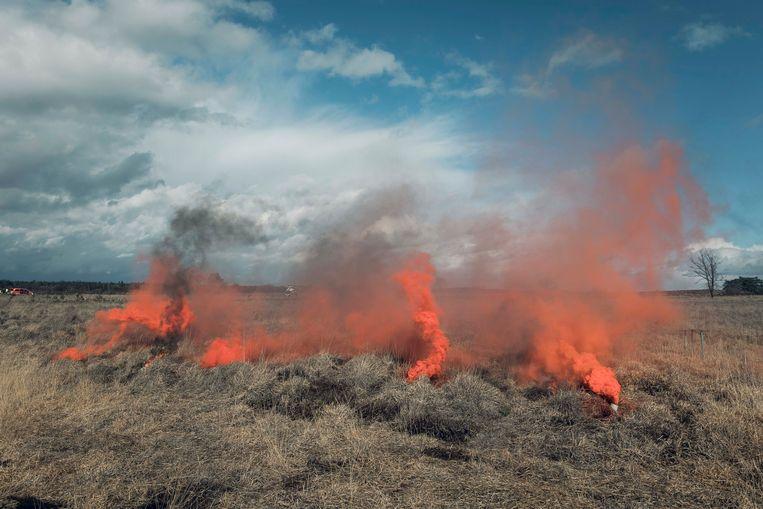 Het lijken wel vlammen, maar in werkelijkheid wordt met gekleurde rook een brand gesimuleerd. Na de regenbui was een vuurtje stoken niet mogelijk.