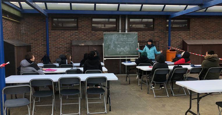 De leerlingen zitten met een dikke jas en trui achter de schoolbanken.