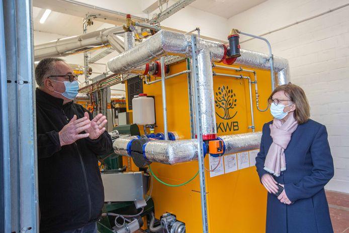 Yves Hendrickx, verantwoordelijke van het Proefcentrum, legt gedeputeerde Monique Swinnen uit hoe de biomassaverwarmingsinstallatie werkt.