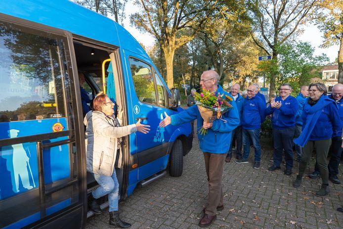 Voorzitter Leo Zeelenberg van het buurtbuscomitŽéŽ ontvangt Marry Haakmeester met een bos bloemen bij de halte aan de Heerenweg in IJhorst.