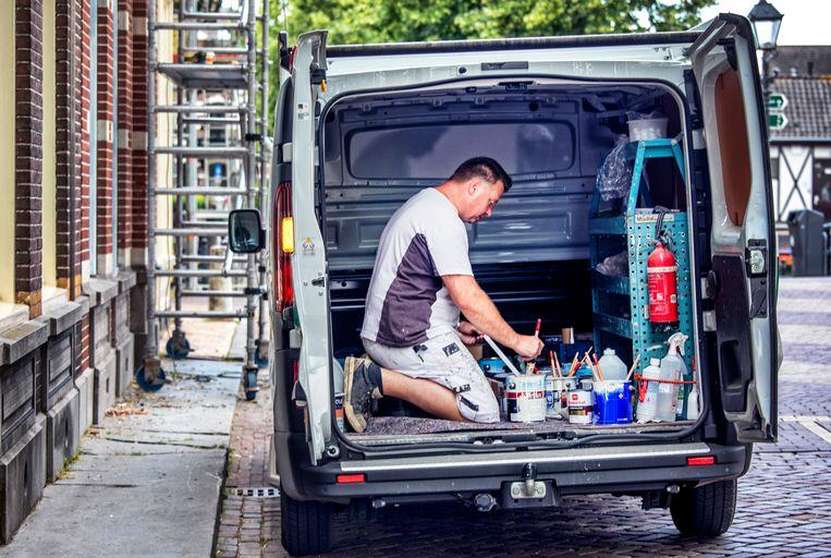 Een zzp-er die als schilder werkt in zijn busje in het centrum van Gorichem.  Beeld Raymond Rutting / de Volkskrant