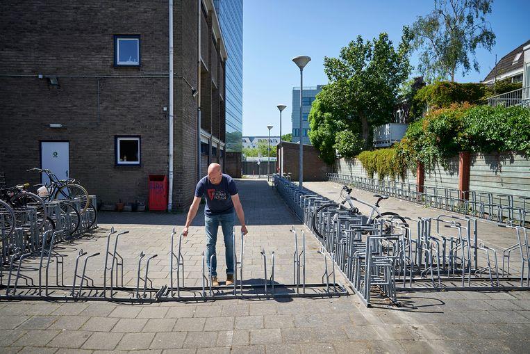 Een medewerker van het Haags Montessori Lyceum richt de fietsenstalling zo in dat de leerlingen zich aan de anderhalvemeterregels kunnen houden. Beeld ANP