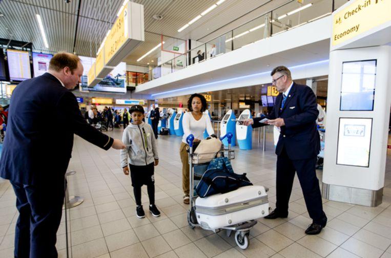 Werknemers van Air France delen flyers uit aan reizigers op Schiphol om hun cao-eisen kracht bij te zetten. Beeld ANP