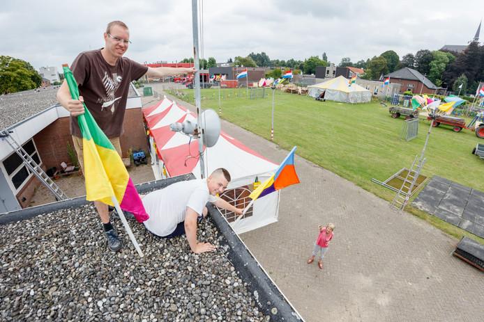 Patrick van Beek (l) en Hans van Haperen hangen op aanwijzing van Corry Roovers de laatste vlaggen op.