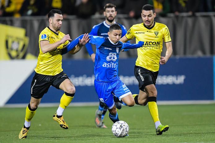 Mauro Junior stoomt op namens Heracles. VVV-speler en Tukker Thomas Bruns (links) probeert hem af te stoppen.
