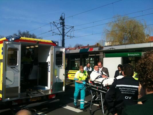 Een gewonde man wordt afgevoerd.
