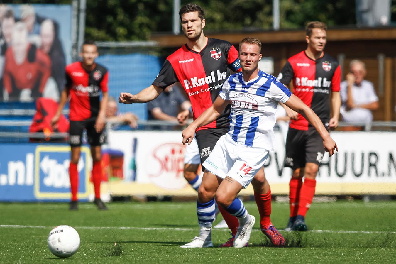 FC Lienden-speler Nick Hak (rechts) wordt in de gaten gehouden door De Treffers-verdediger Pim Balkestein.