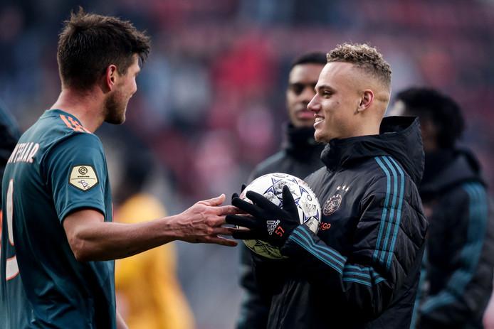 Noa Lang mag de bal meenemen na zijn hattrick tegen FC Twente en wordt gefeliciteerd door Klaas-Jan Huntelaar.