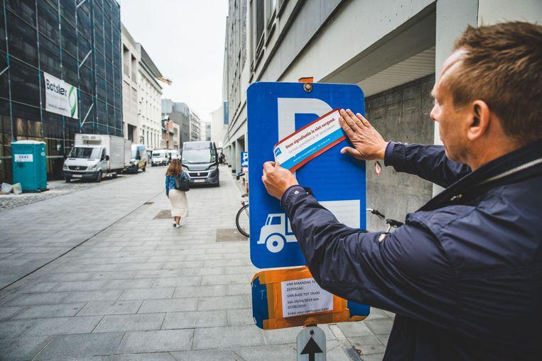 Een controleur brengt een sticker aan waardoor het parkeerverbod niet langer geldig is