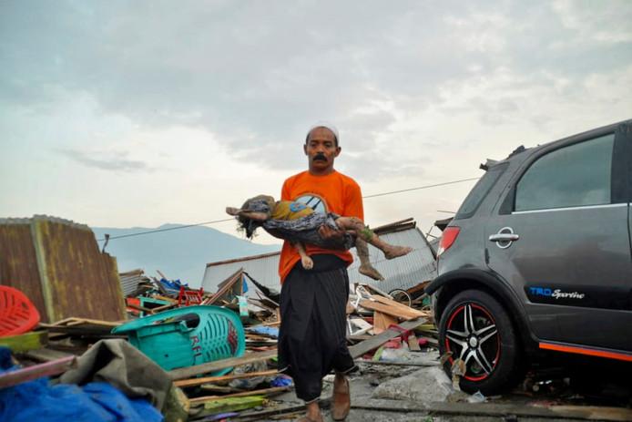 Een man draagt het lichaam van een kind dat overvallen werd door de tsunami in Palu, Sulawesi en het niet overleefde.