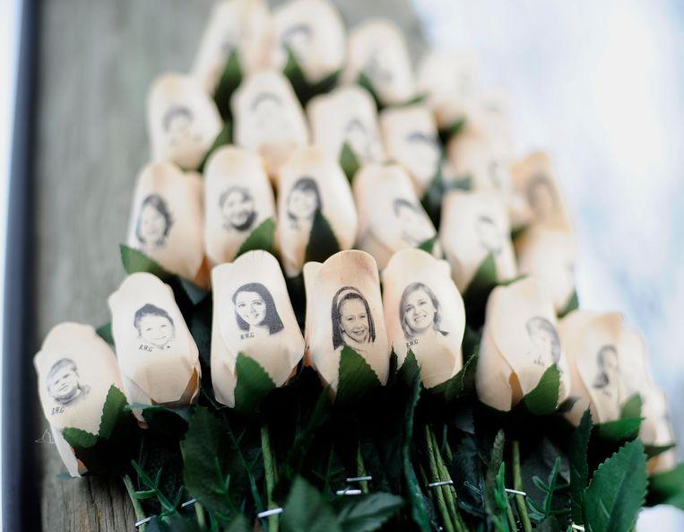 Rozen met de foto's van de slachtoffers.