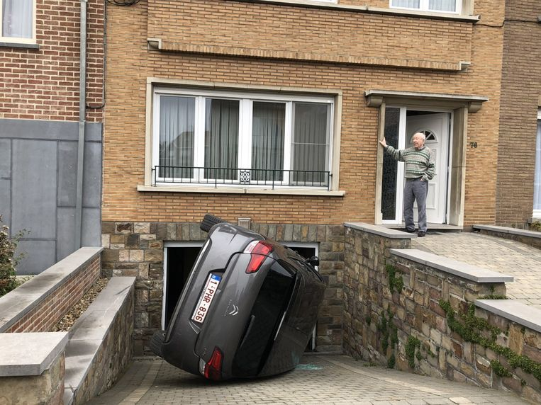 Henri Pauwels aanschouwt zijn gekantelde wagen. De man komt met de schrik vrij.
