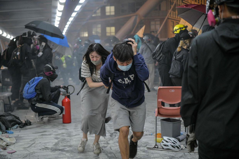 Opstandelingen die proberen uit te breken worden telkens met een stortregen van traangasgranaten uit elkaar gejaagd, terug richting campus of in de armen van de politie, die ze arresteert. Beeld AFP