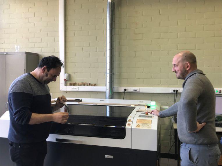 Kurt Melis (links) en Thomas Van Kerckhoven (rechts) aan de lasercutter