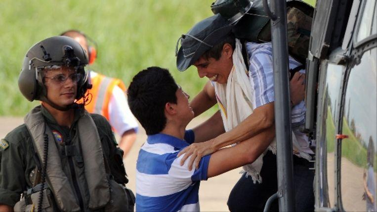 Alan Jara (r) valt zijn zoon in de armen bij aankomst op het vliegveld Villavicencio, 90 kilometer ten zuiden van Bogotá. (AFP) Beeld AFP