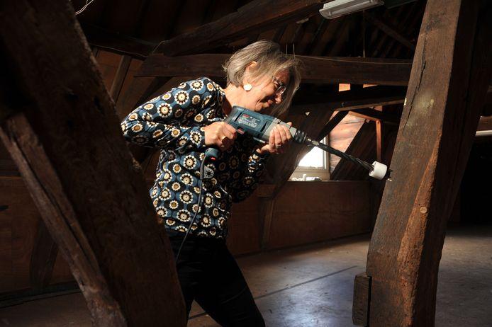 Bouwhistoricus Christine Weijs onderzoekt de ouderdom van panden door staafvormige stukjes hout uit oude balken te boren.