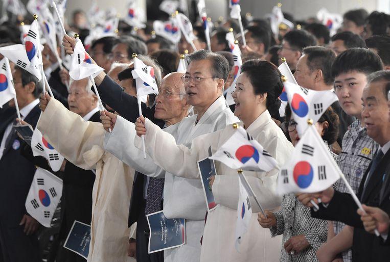 De Zuid-Koreaanse president Moon Jae-in en first lady Kim Jung-sook zwaaien met de nationale vlag tijdens een herdenkingsbijeenkomst ter ere van de bevrijding van Zuid-Korea in 1945, na een 35-jarige bezetting door Japan.