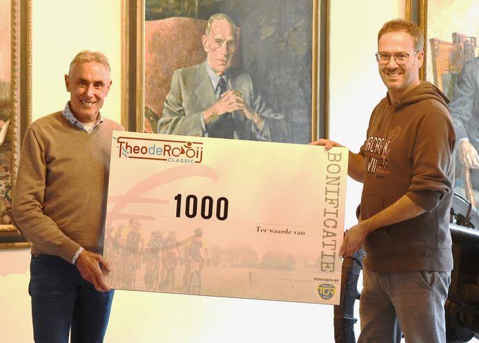 Theo de Rooij overhandigt een cheque van 1000 euro aan Rogier Veltrop.