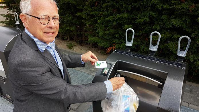 Wethouder Henk Kielman gebruikt een Saver-pasje om een plasticcontainer te openen. ,,We proberen de afvalverwerking kostendekkend te houden. We vinden het belangrijk dat er geen burgers buiten de boot vallen omdat ze in geldnood komen.''