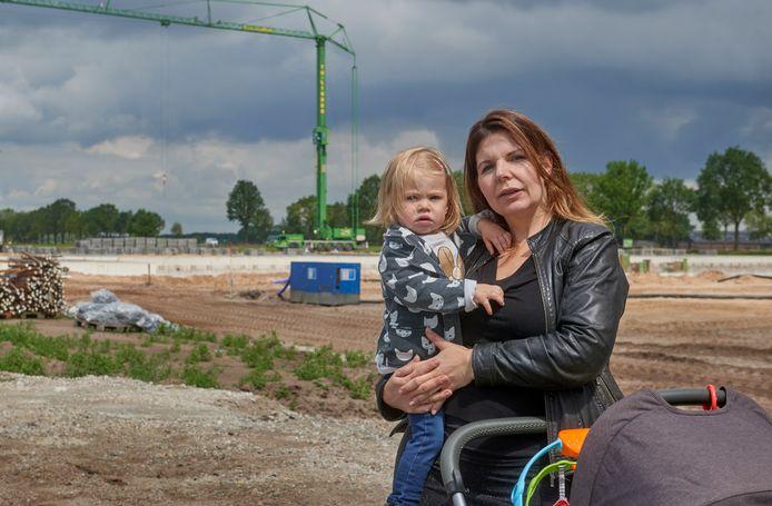 Olga Meulenbroek met dochtertje Sanne bij de megastal in aanbouw aan de Schuifelenberg, in juni. Met buurtbewoners springt zij op de bres voor het woon- en leefklimaat.