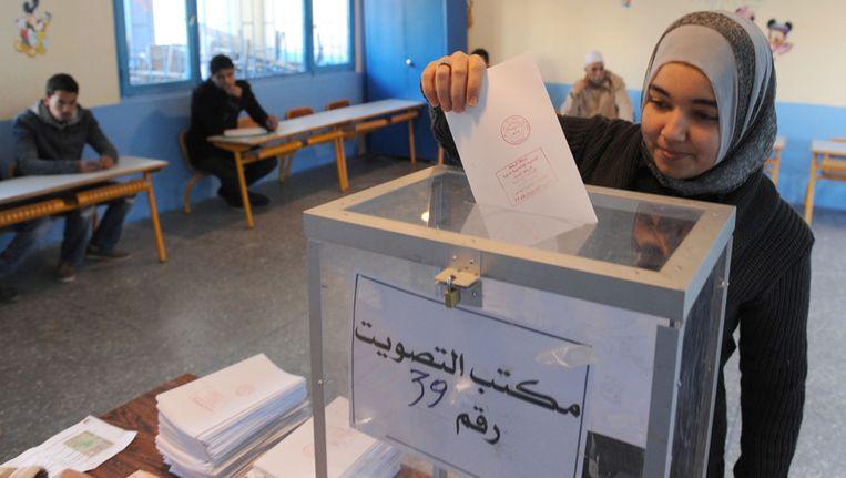 Marokkaanse kiezer in Rabat levert een een stembiljet in. Beeld afp
