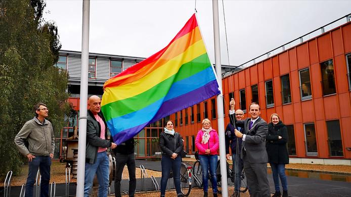 Burgemeester Bram van Hemmen en Anton van Rees (PvdA) hijsen de regenboogvlag in Sliedrecht. Op de achtergrond: Vincent Prins (CDA), Maria Stam (PRO Sliedrecht), Marja Bouwmans (D66), René de Munck (D66) en Esther Gruppen (PvdA).