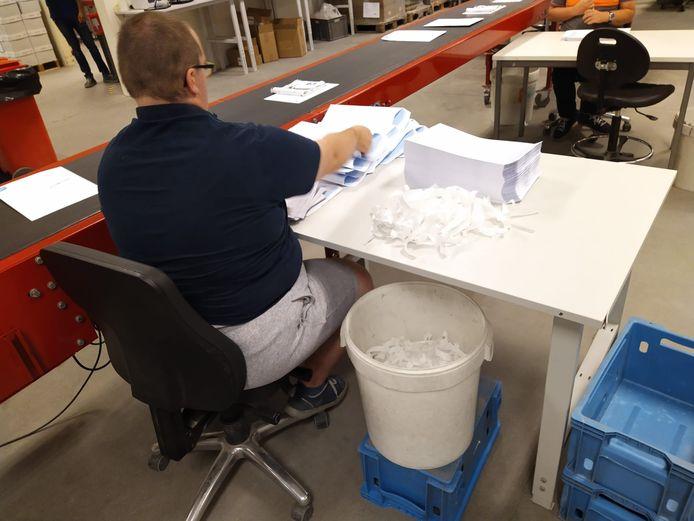 Bij maatwerkbedrijf Mirto worden de mondmaskers en de filters samengevoegd en in enveloppen gestopt.