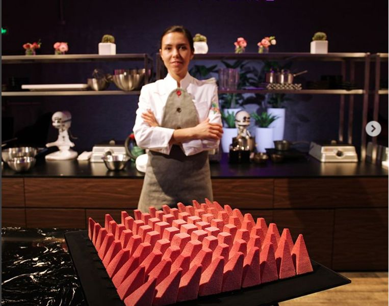 Dinara Kasko voor een van haar creaties, een cake bestaande uit 81 elementen die via een algoritme gevormd zijn. Het geheel is gemaakt met roze 'ruby' chocolade.