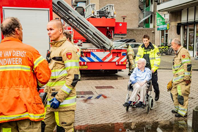 Een bewoner wordt in zijn rolstoel geëvacueerd.