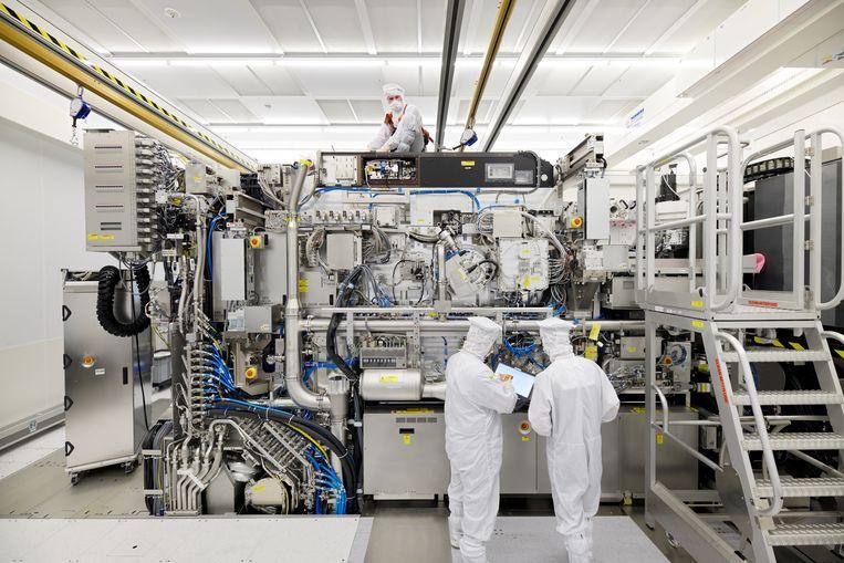 Werknemers van ASML bij een chipmachine, in Veldhoven.  Beeld Reuters