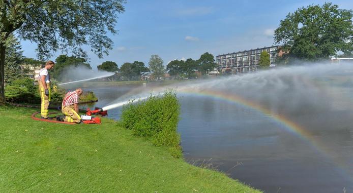 De brandweer spuit water in de rivier zodat er meer zuurstof in de vijver komt. Foto: Pim Velthuizen.