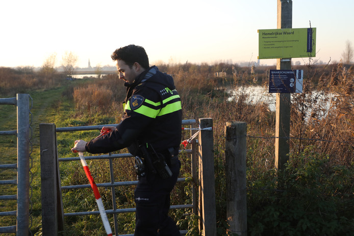 Een politieagent zet het gebied af met lint.