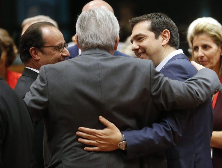Tsipras omarmt Juncker tijdens de bijeenkomst van de politieke leiders van de eurozone afgelopen zondag. Beeld ap