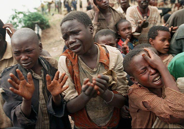 Rwandese kinderen smeken in 1994 Congolese soldaten of ze de brug tussen Congo (destijds Zaïre) en Rwanda over mogen steken. Hun moeders staken de brug eerder al over. Beeld AP