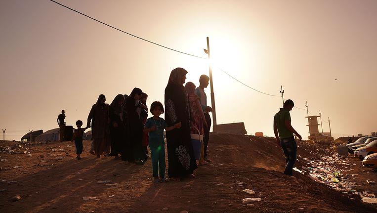 Een Irakese familie wacht buiten een vluchtelingenkamp. Beeld getty