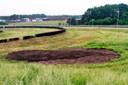 Op de plek waar net na de start op Breda Airport een reclamevliegtuig neerstortte, herinneren alleen net gestorte grond en witte markeringspaaltjes nog aan het drama.