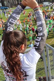 1200 koprollende kinderen in het gras bij wereldrecord capoeirales in Nieuwegein