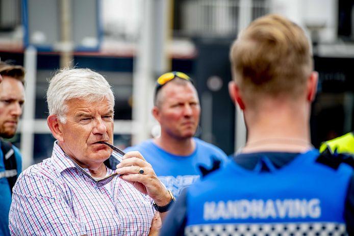 De Haagse burgemeester Jan van Zanen tijdens een gesprek met handhavers en verkeersregelaars over de knelpunten van Scheveningen. Hij is eerder dan gepland van vakantie teruggekomen.