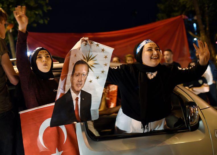 Een aanhangster van Erdogan zwaait met zijn portret op het Taksimplein in Istanbul.