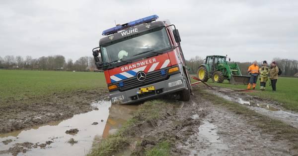Brandweer Wijhe wil helpen bij aanrijding in Olst, maar komt vast te zitten in weiland.